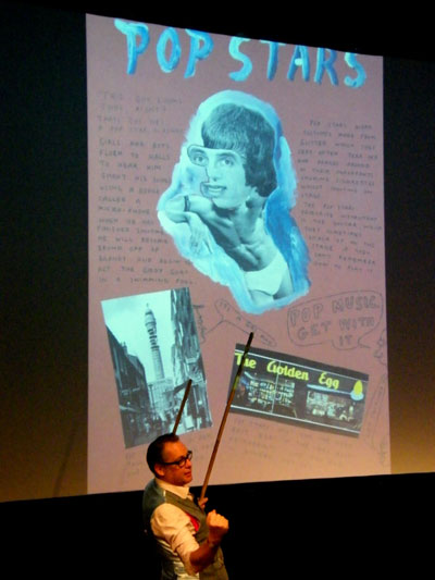 Vic Reeves using a broom as pointer whilst explainig about Pop Stars.   Photo: Minako Jackson