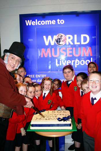Sir William Brown, played by World Museum's resident actor Paul Netterfield cuts the cake for Holy Cross pupils